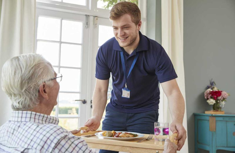 Carer helping man in his home