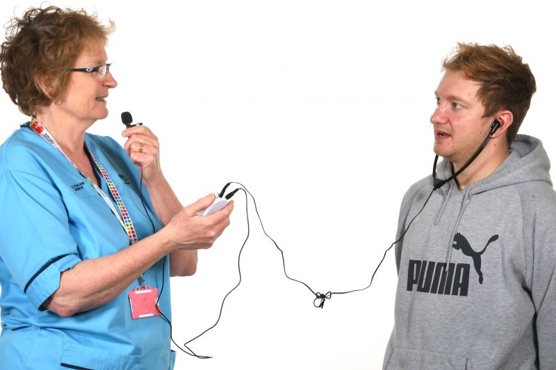 Picture of an NHS worker using a personal listener with a person with sensory impairment