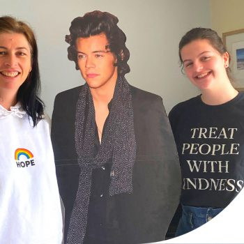 A picture of a mother and daughter posing with a cardboard cutout of Harry Styles