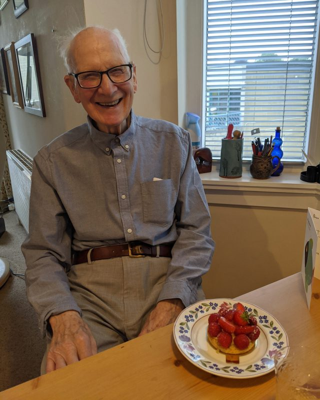 A smiling man with grey hair and glasses sitting in front of a plate of fruit and pancakes