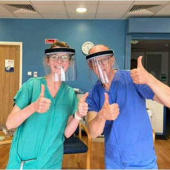 a man and a woman wearing scrubs giving the thumbs up sign while wearing face visors