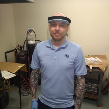 a man in a blue polo shirt wearing a clear face visor